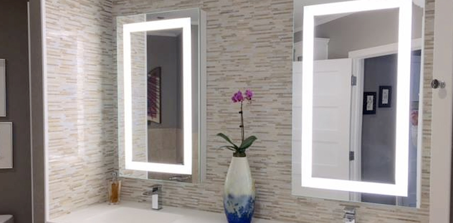 tiled bathroom with two lighted mirrors