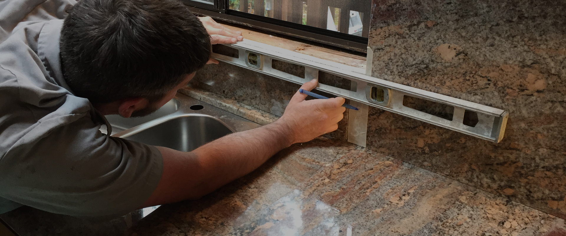 man meausring backsplash area behind sink